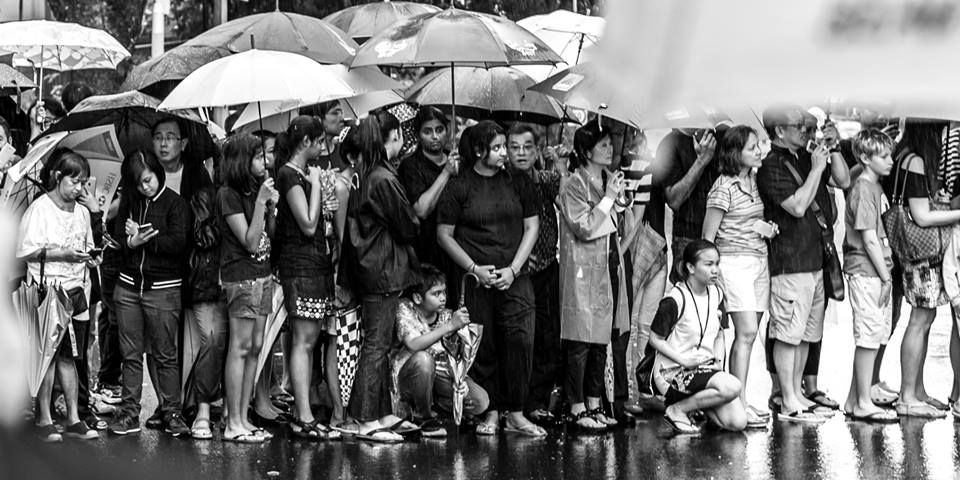 People waiting for hours in the rain to catch a glimpse of Lee Kuan Yew as he made his final journey through his city, Singapore